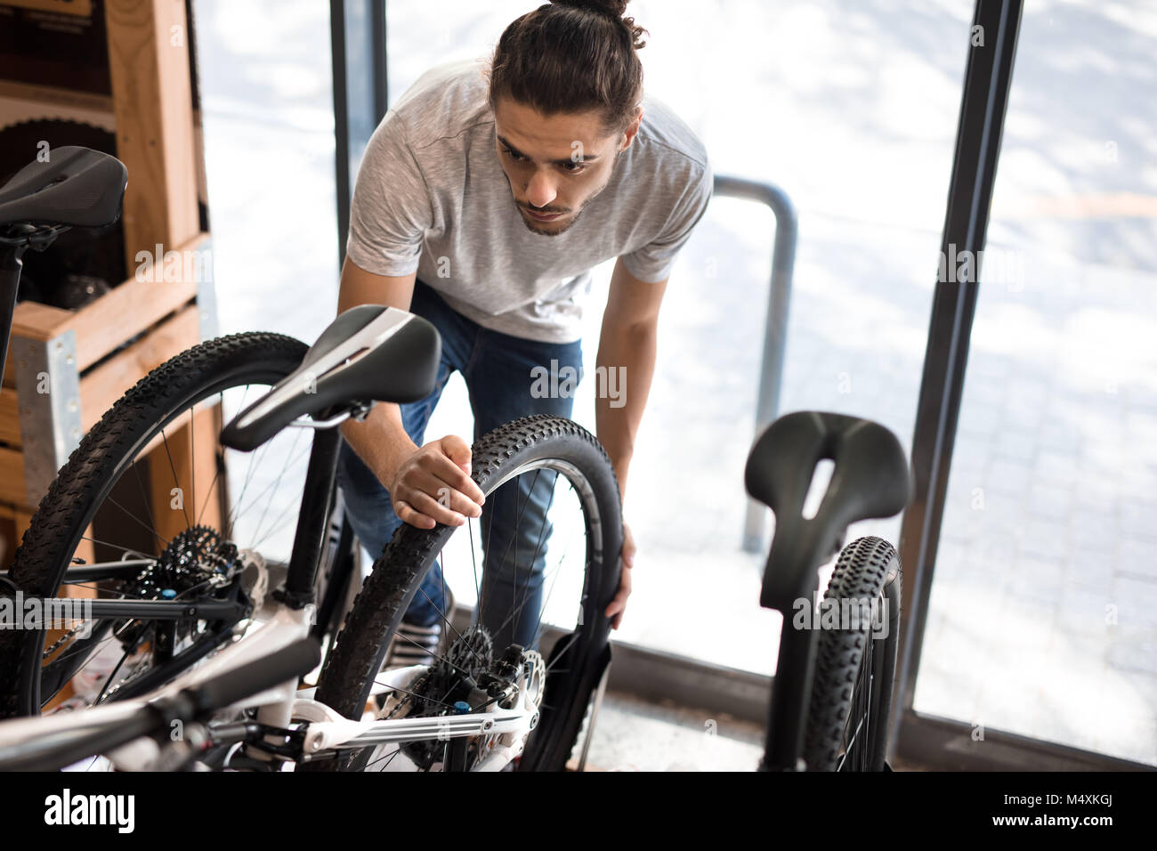 Man inspecting a bicycle wheel for alignment. Mechanic working on fixing a bicycle in workshop. - Stock Image
