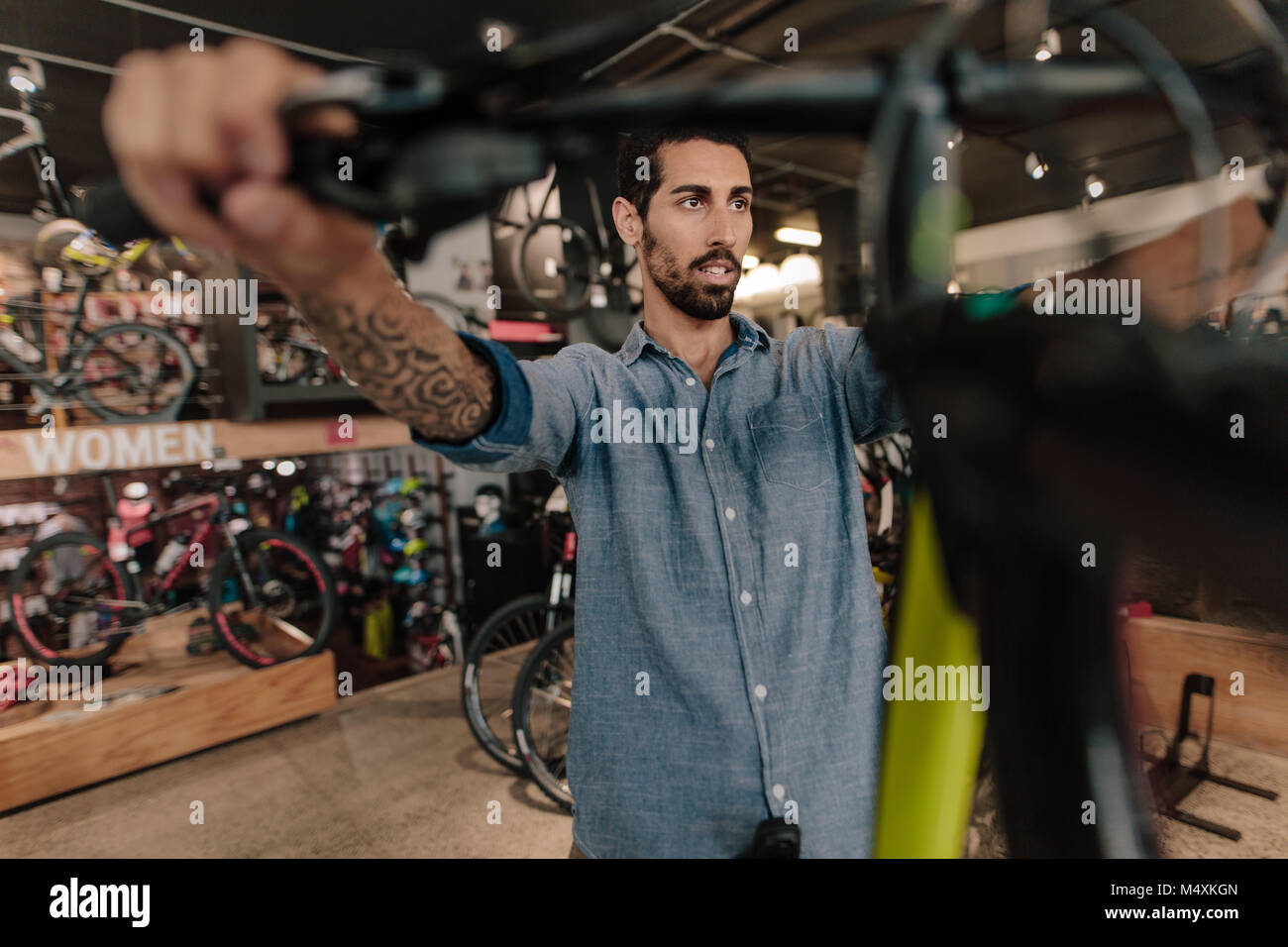 Man inspecting a bicycle handle for alignment at a showroom. Man at a bicycle showroom looking at bicycles. - Stock Image