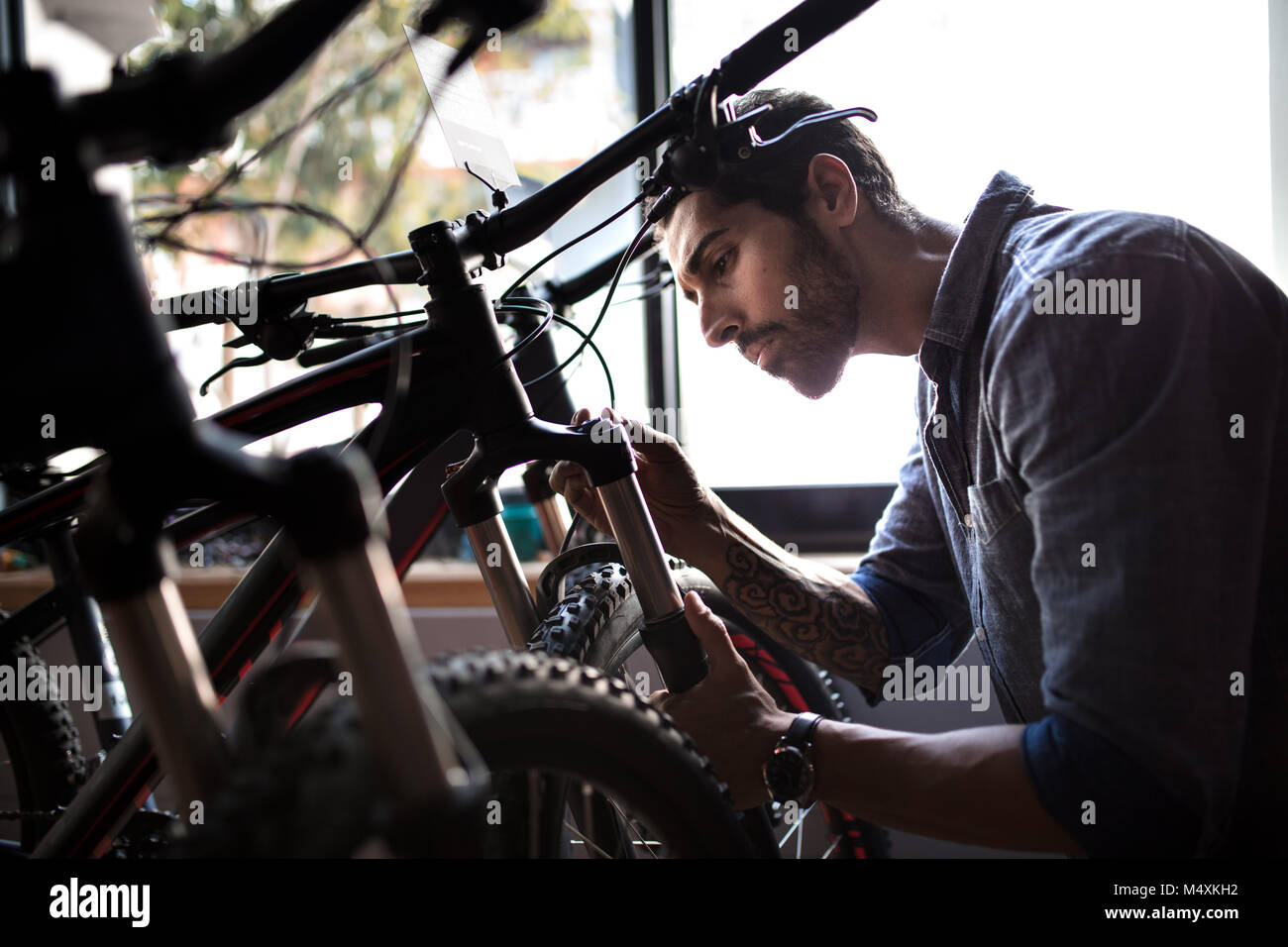 Mechanic inspecting a bicycle shock absorbers inside a showroom. Man at a bicycle showroom making repairs. - Stock Image