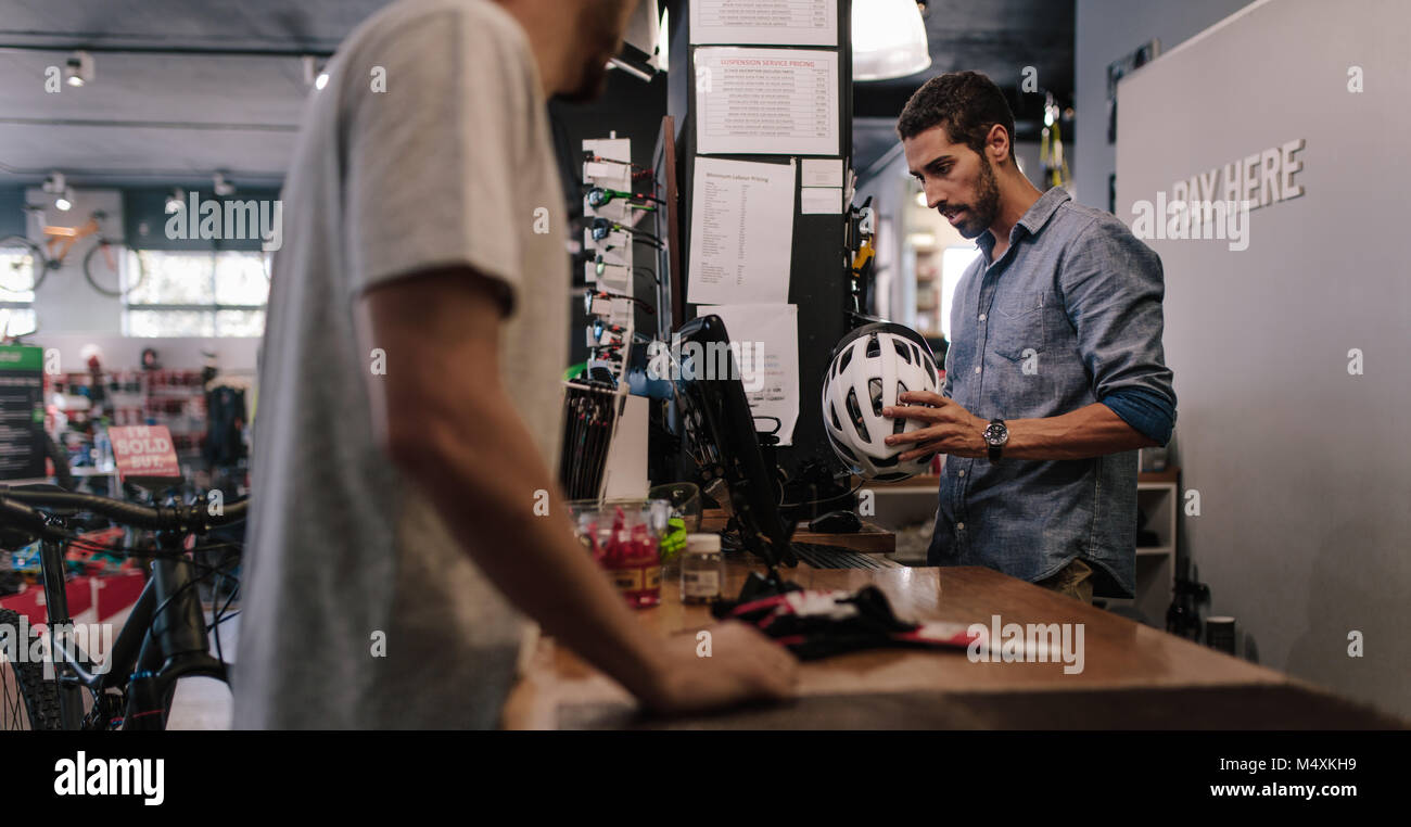 Man at the billing counter selling a bicycle helmet. Sport shop owner making a bill for sale of helmet using computer. - Stock Image