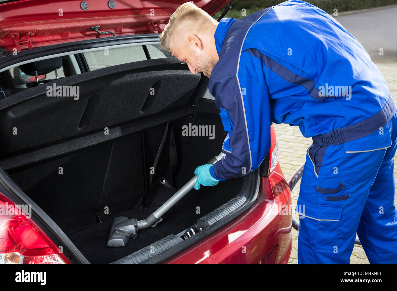 Happy Young Man Vacuuming Car Trunk With Vacuum Cleaner - Stock Image
