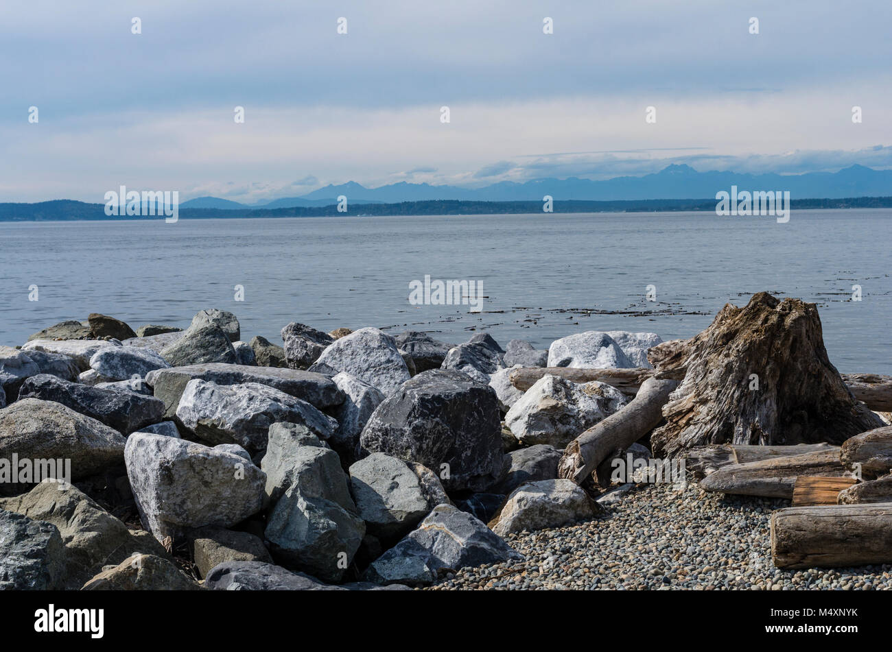 Rock rip rap along the Seattle waterfront with the Olympic Mountains in the background.  Seattle, Washington - Stock Image