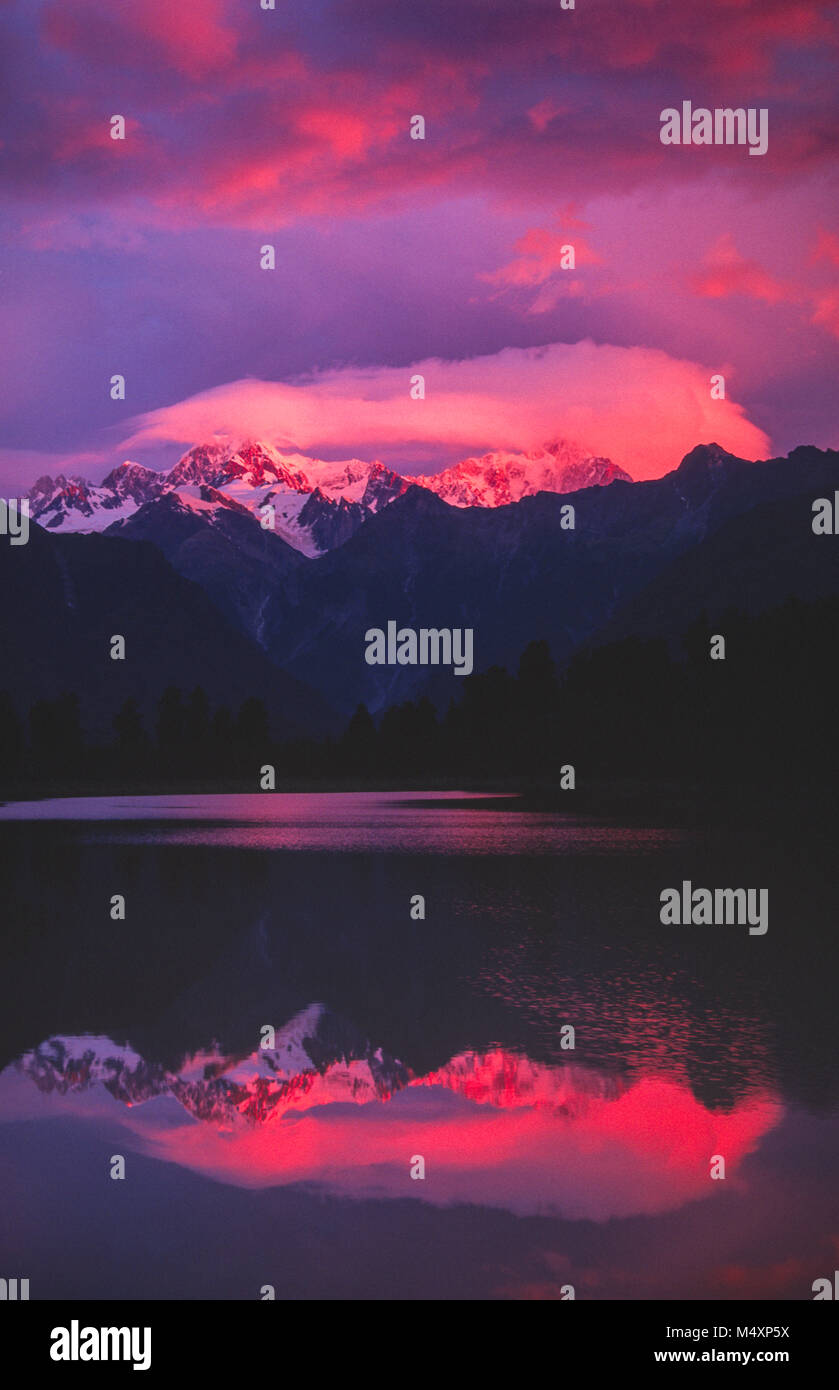 Sunset reflection of Mt Tasman and Mt Cook, Lake Matheson, Westland National Park, South Island, New Zealand. - Stock Image
