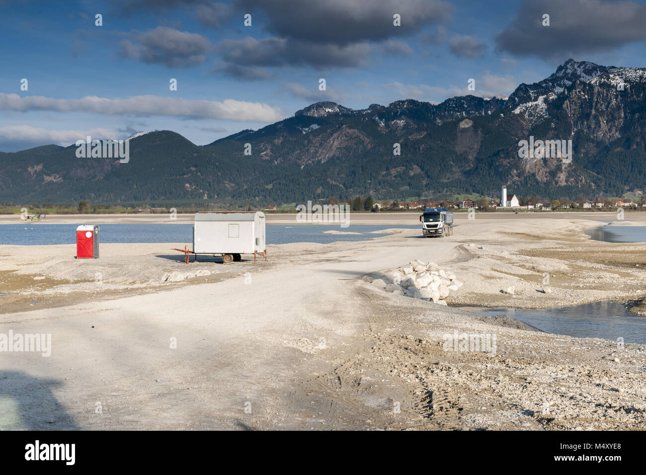 Empty forggensee with construction vehicle and toilet house - Stock Image