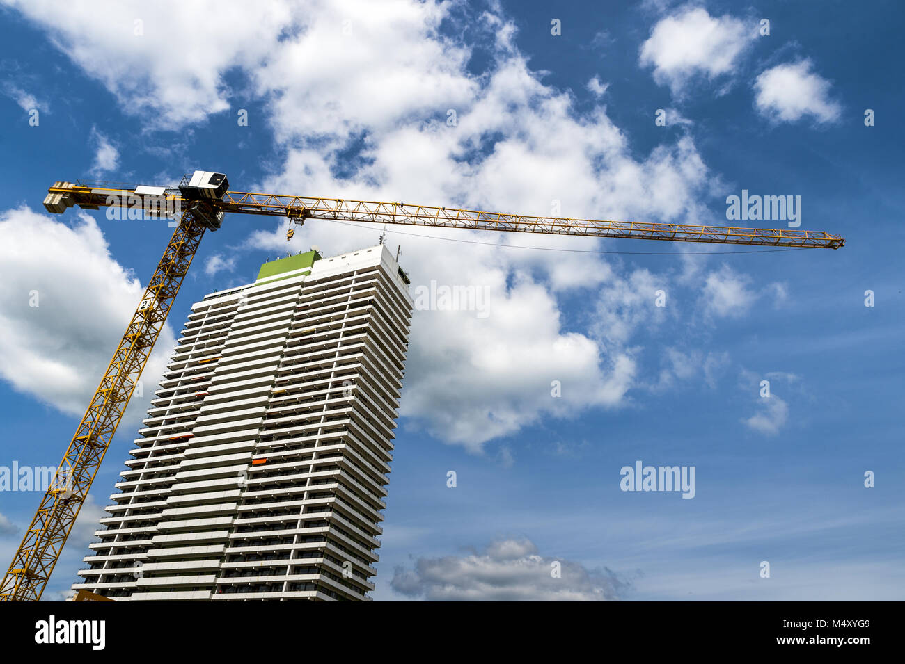 A crane and a high-rise against a blue sky - Stock Image