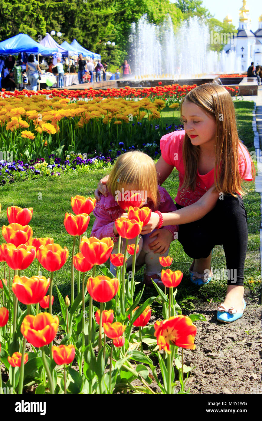 The older sister teaches the younger to smell tulips - Stock Image