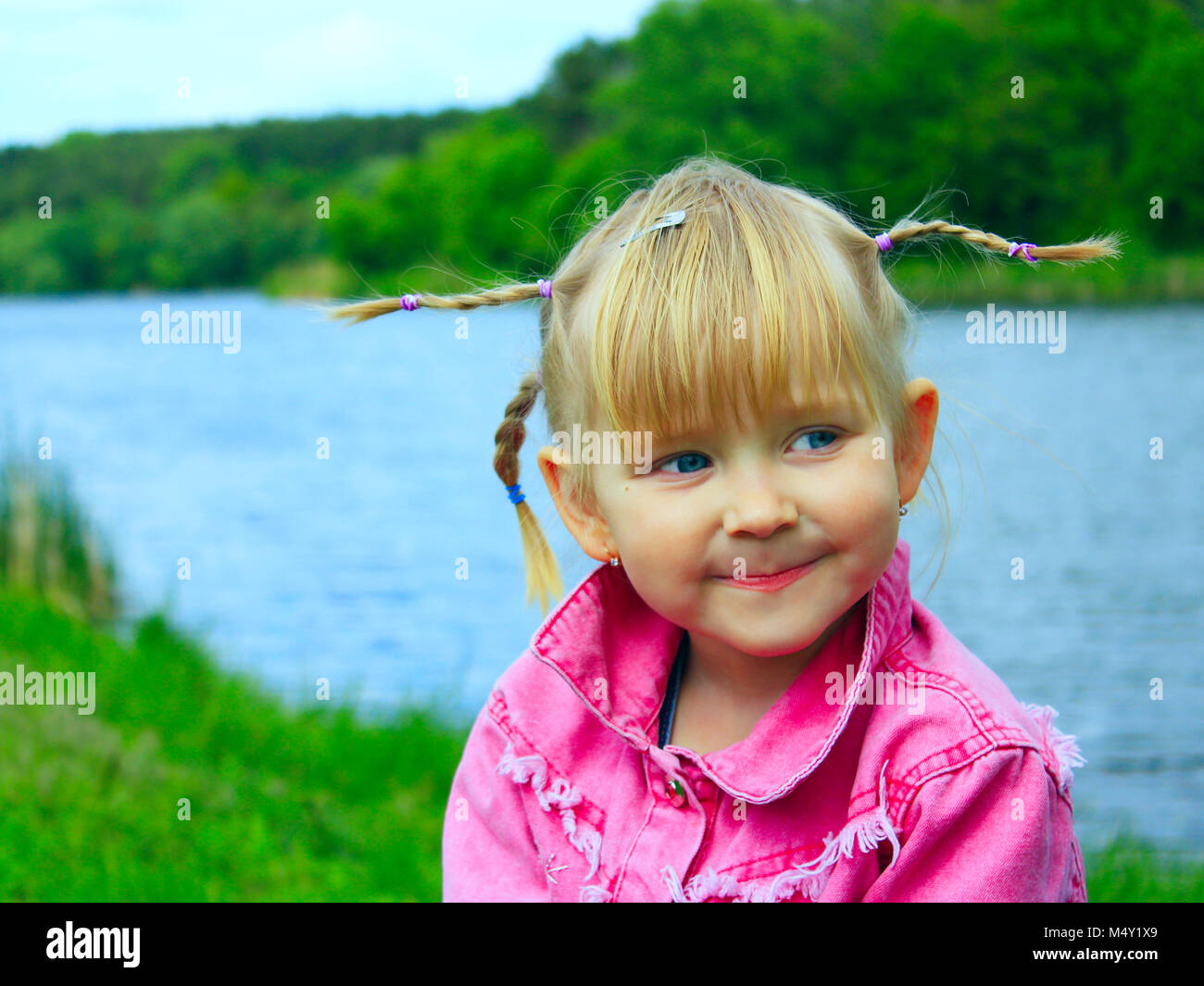 pretty smiling baby girl with nice plaits - Stock Image