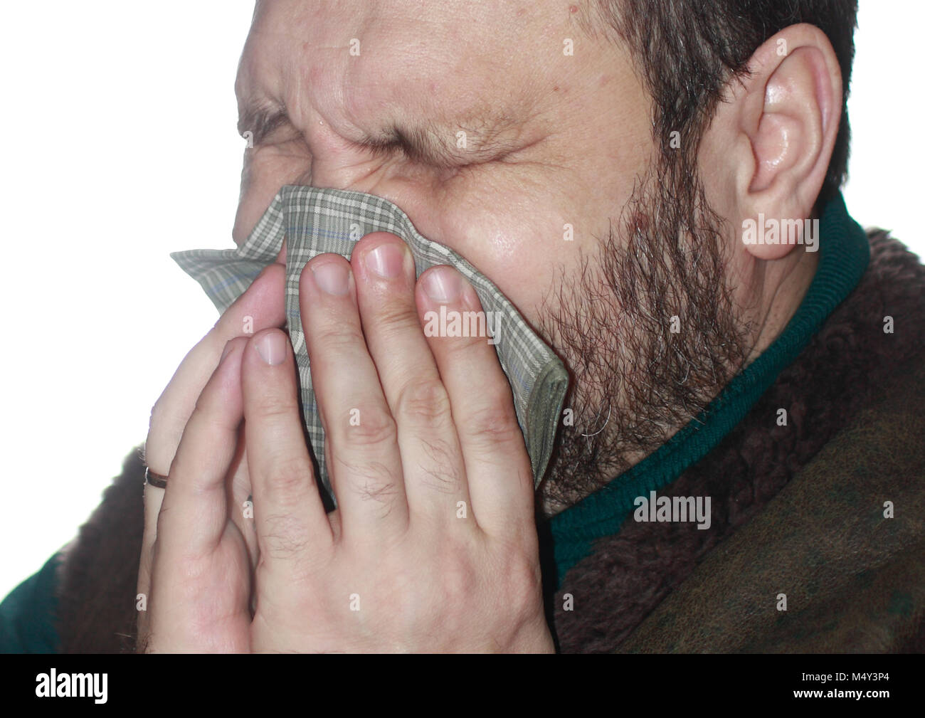The sick man with the sneezes in a handkerchief - Stock Image