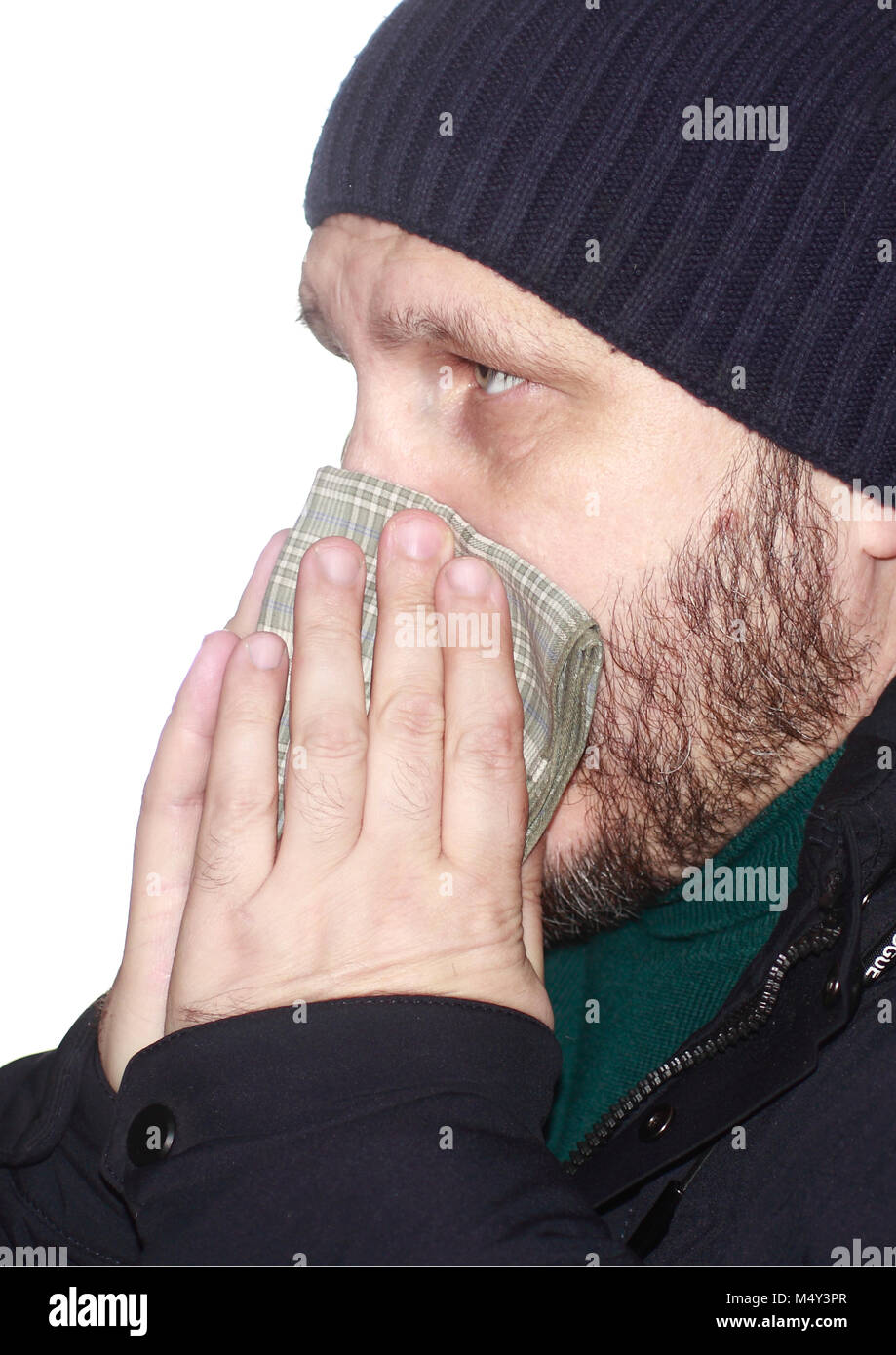 Sick bearded man blowing his nose in a handkerchief - Stock Image