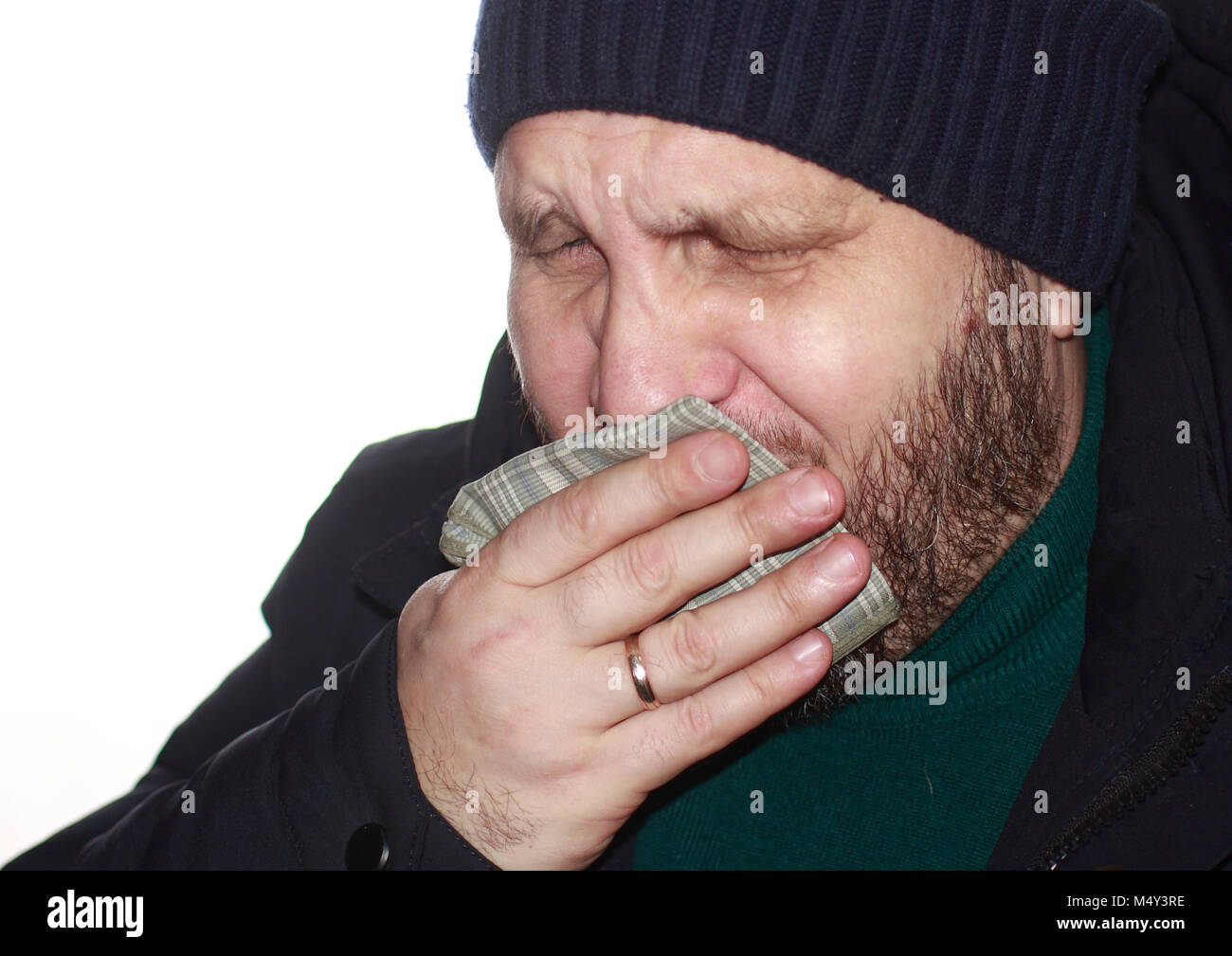 Bearded man coughs, covering his mouth with a handkerchief - Stock Image