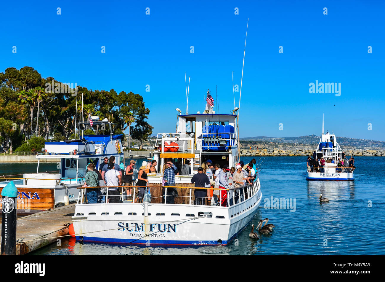 Tourists board a fishing boat at Dana Point Harbor in Orange County, CA. - Stock Image