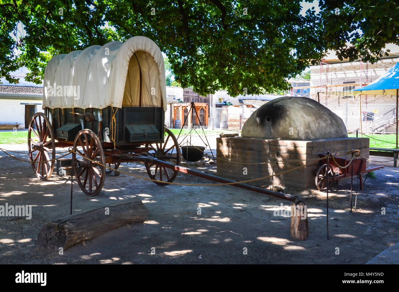 Covered wagon and beehive oven in outdoor exhibit at Sutter's Fort Historical Site near Sacramento, CA. - Stock Image