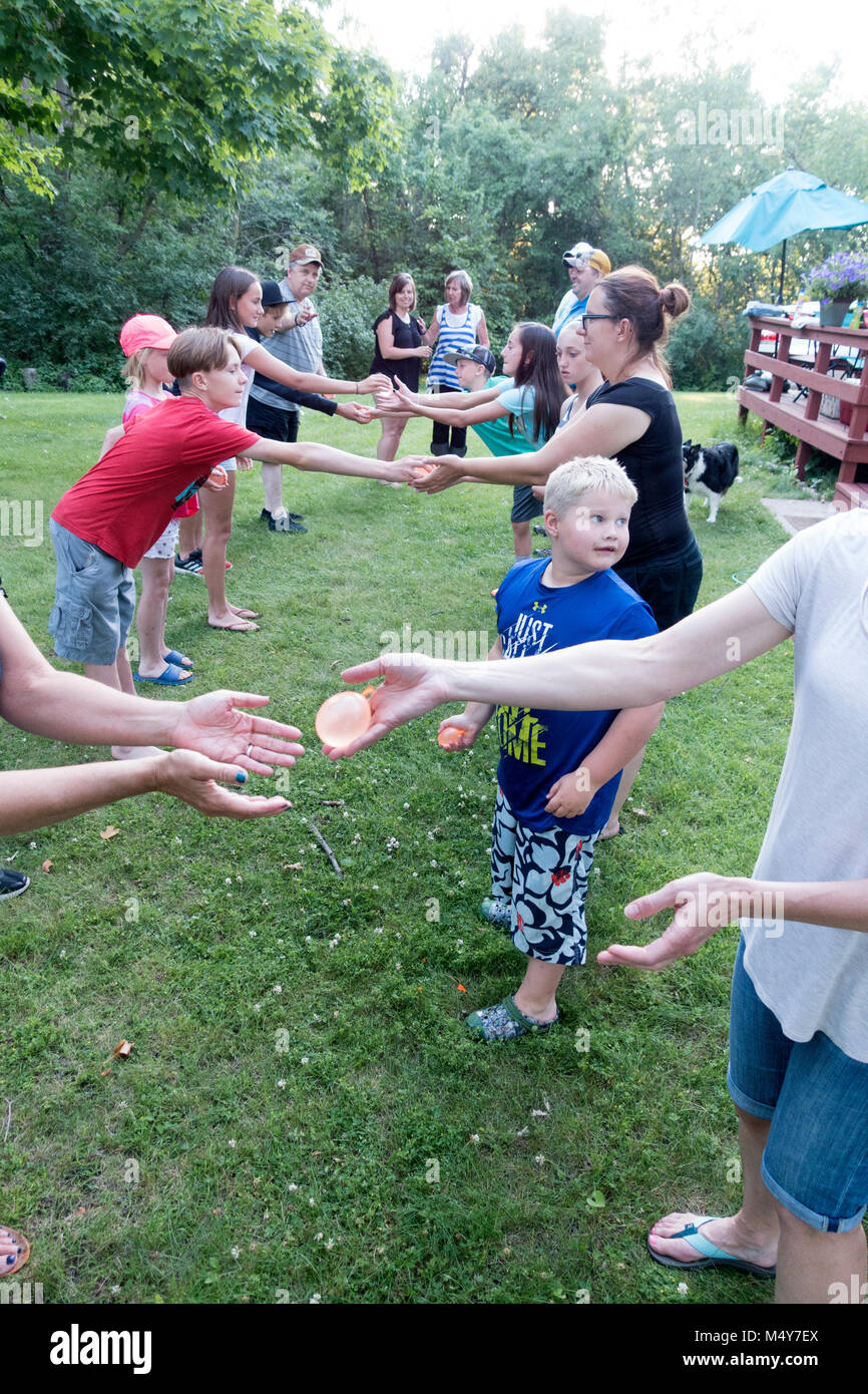 Extended family of three generations starting a water balloon toss game. Clitherall Minnesota MN USA - Stock Image