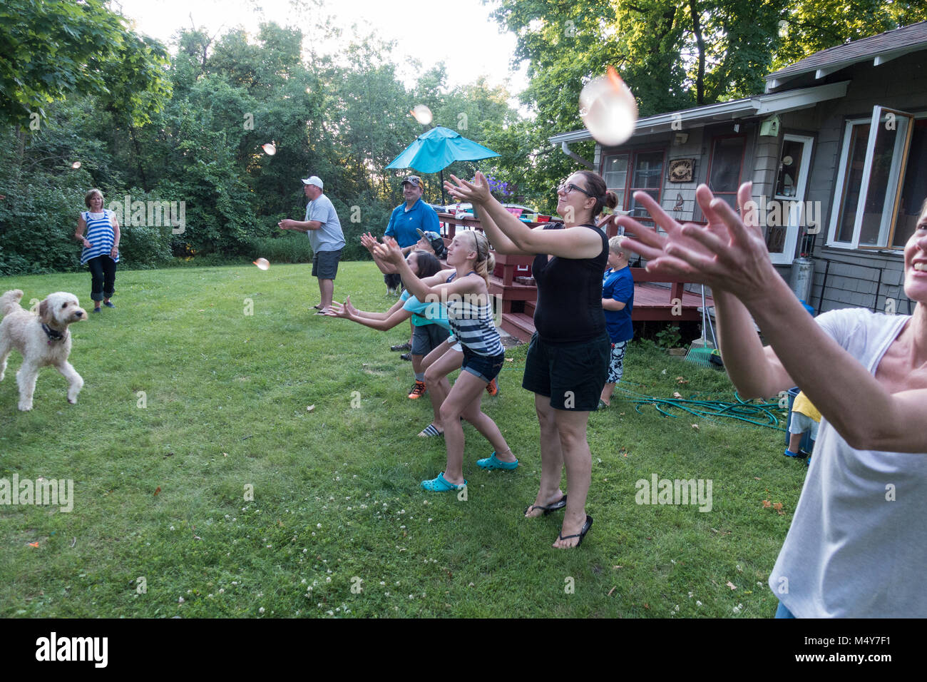Extended family of three generations and a dog playing water balloon toss. Clitherall Minnesota MN USA - Stock Image