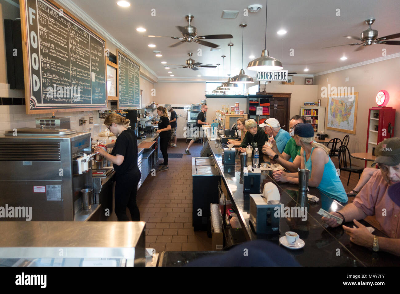 Workers preparing coffee and ice cream goodies for customers enjoying themselves at the Justice Two Coffeehouse - Stock Image