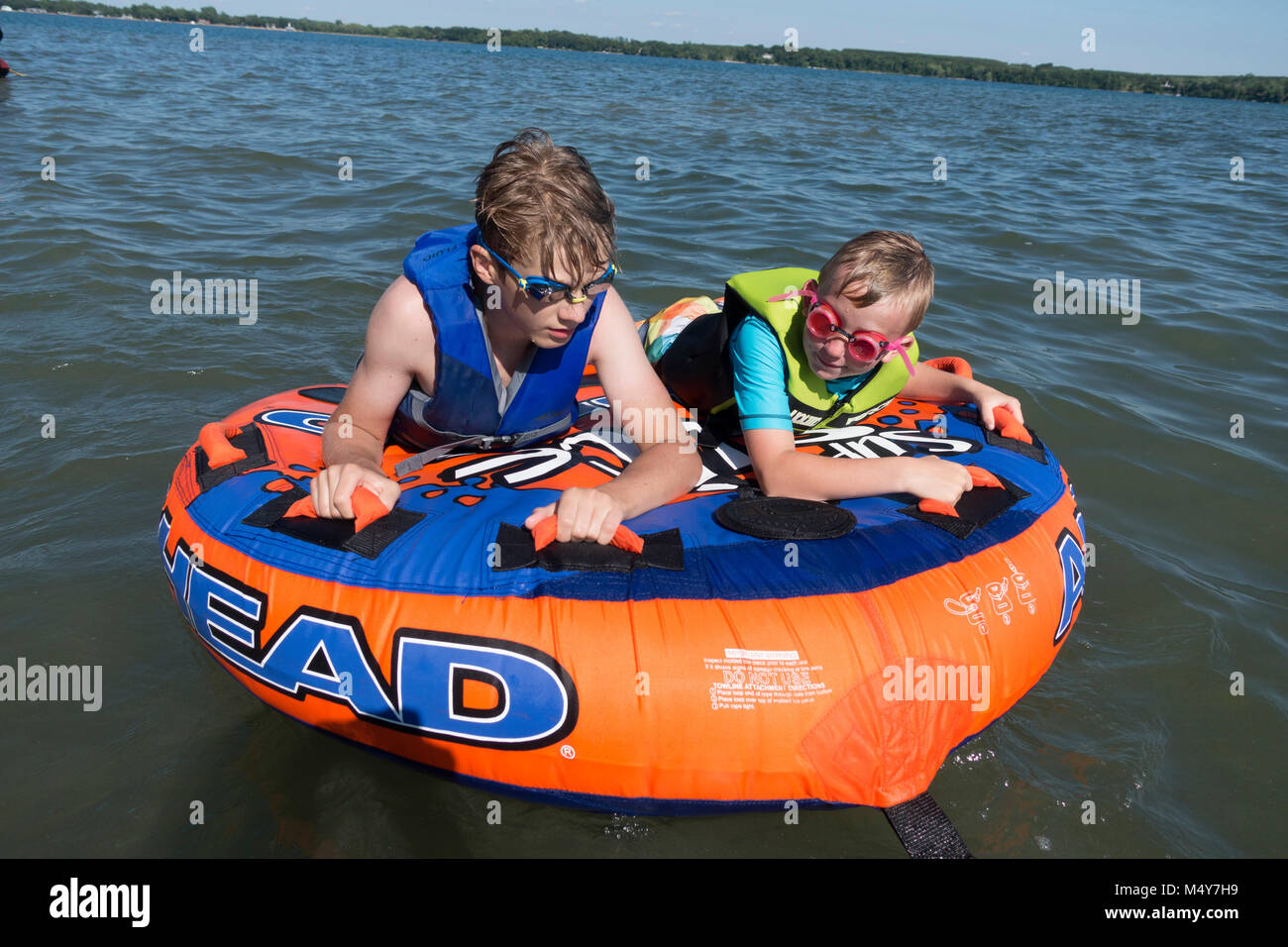 Two boys wearing goggles and life vests hanging on to their water donut waiting for the ride of their lives. Clitherall - Stock Image