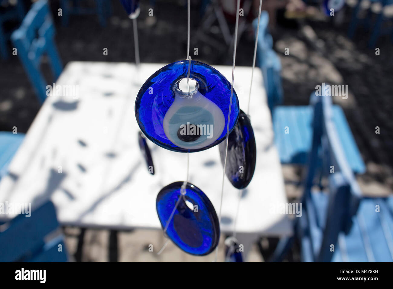 Hung, decorative evil eyes with blue, wooden chairs and white table in Cunda (Alibey) island. - Stock Image