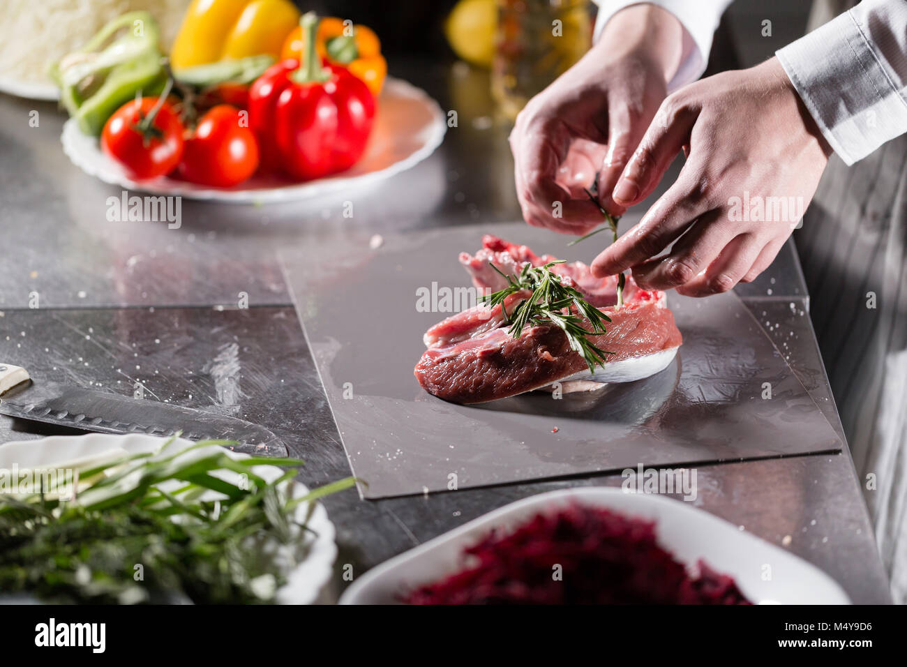 Rare lambs ready for marinade with rosemary. Cooking with fire in frying pan. Professional chef in a kitchen of - Stock Image