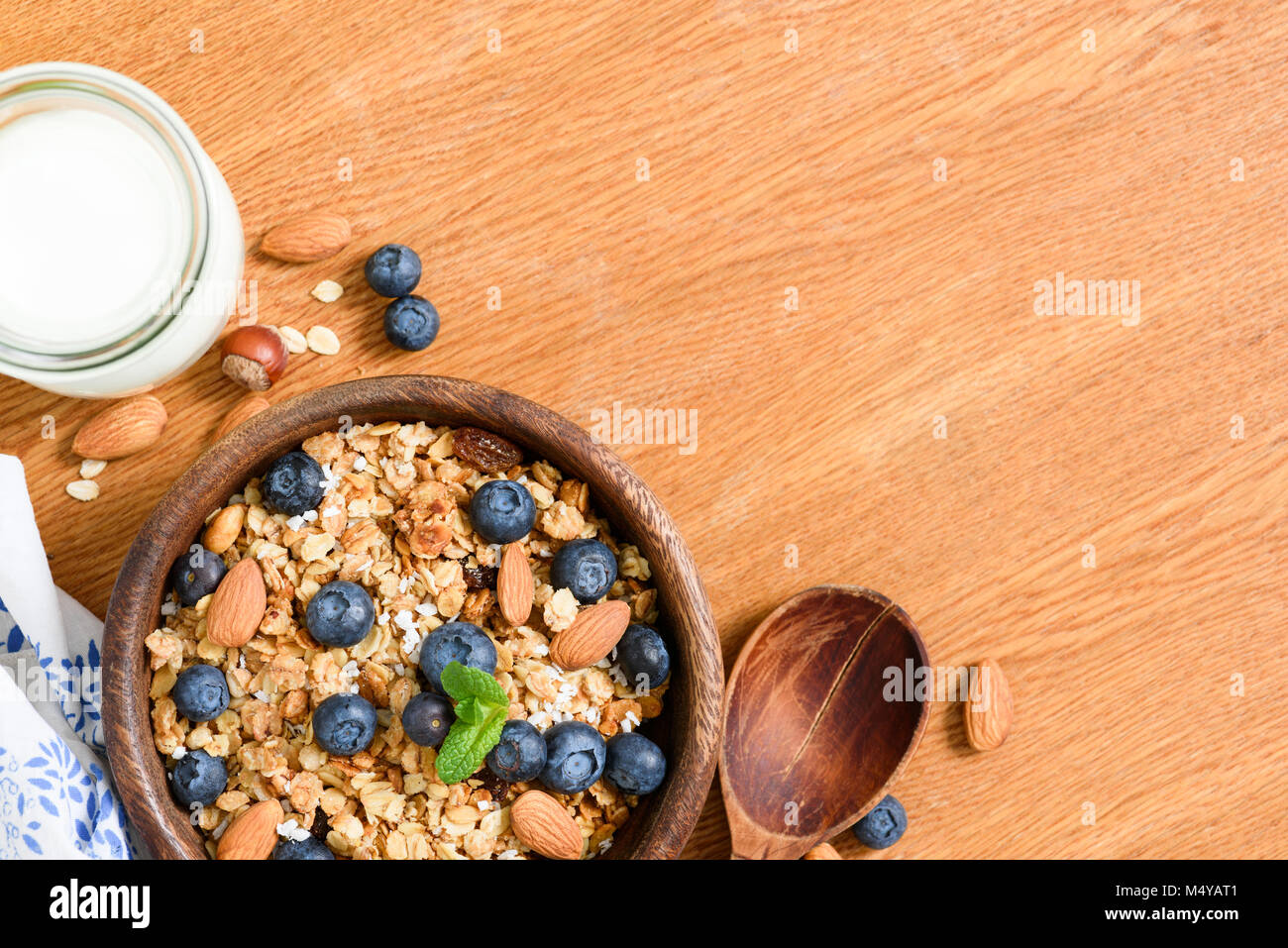 Granola with nuts and berries, milk on wooden table. Top view with copy space for text. Concept of weight loss diet, Stock Photo