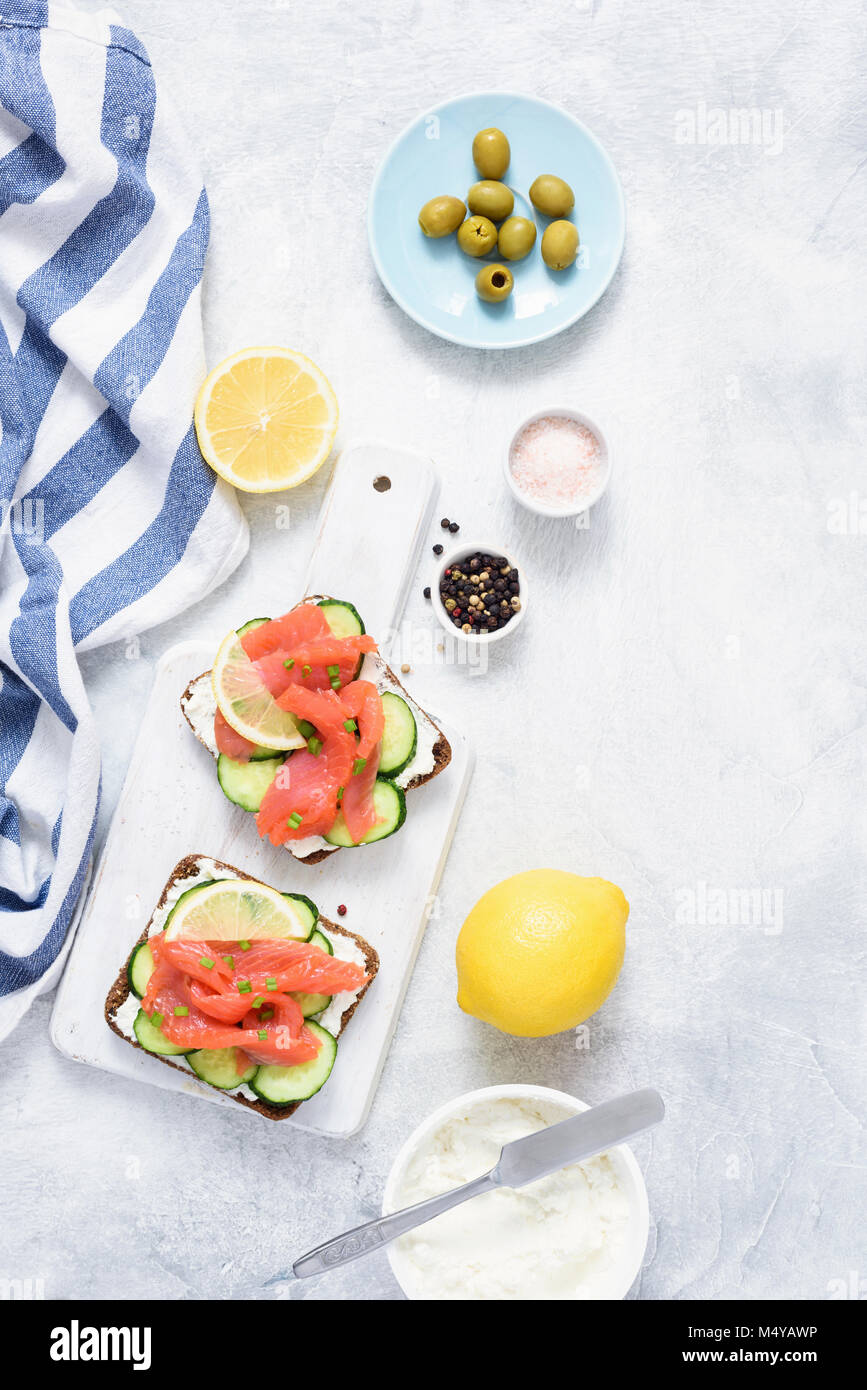 Sandwiches with salmon, cucumber and cream cheese on white background. Top view. Mediterranean cuisine - Stock Image