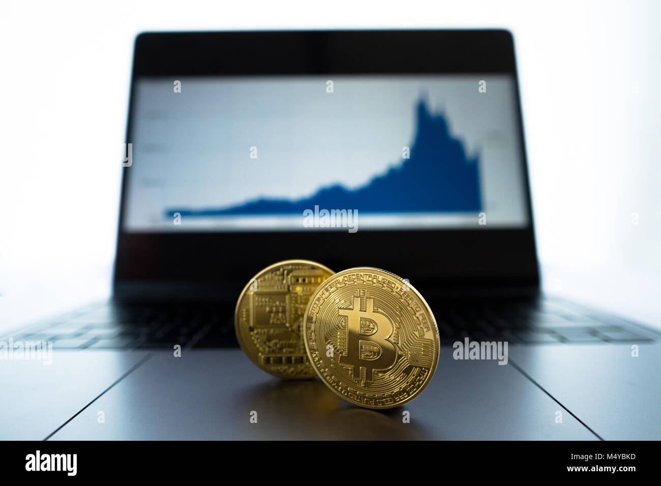 Physical gold Bitcoin with shallow depth of field sitting in front of laptop showing area chart of historic Bitcoin - Stock Image