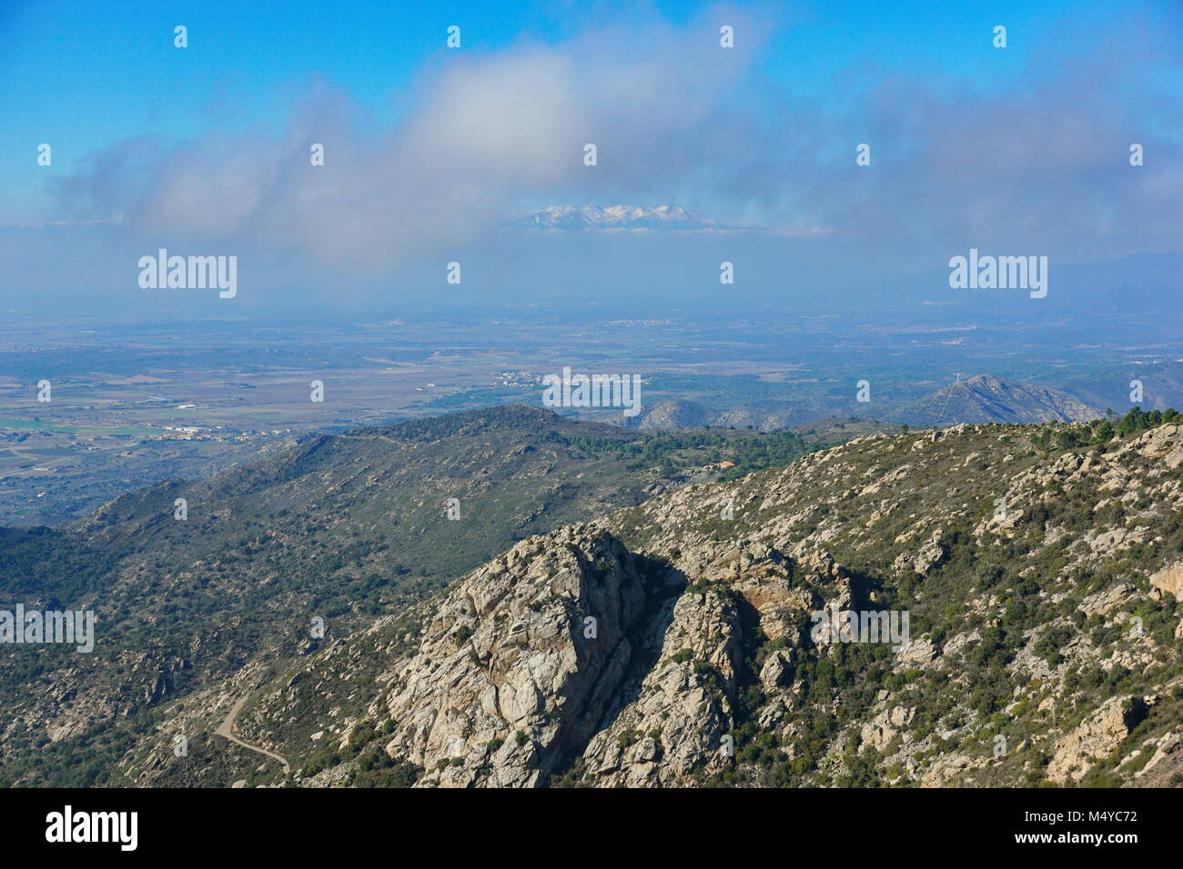 Landscape from the top of Verdera mountain in Spain with the Canigou mountain appears in the sky between clouds, - Stock Image