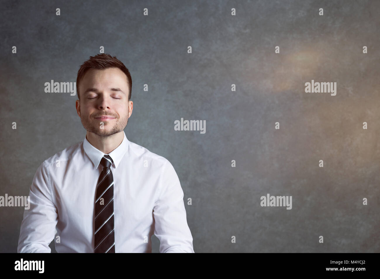Relaxed and balanced businessman with a smile - Stock Image