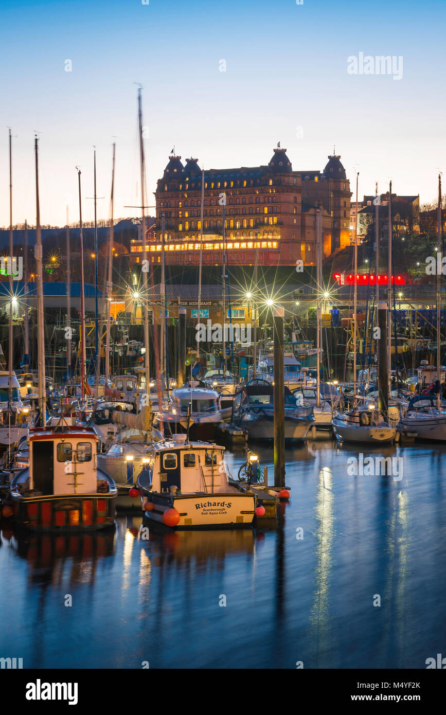Scarborough harbour, view at dusk of the harbour area and, beyond, the Grand Hotel sited on the skyline of Scarborough, - Stock Image