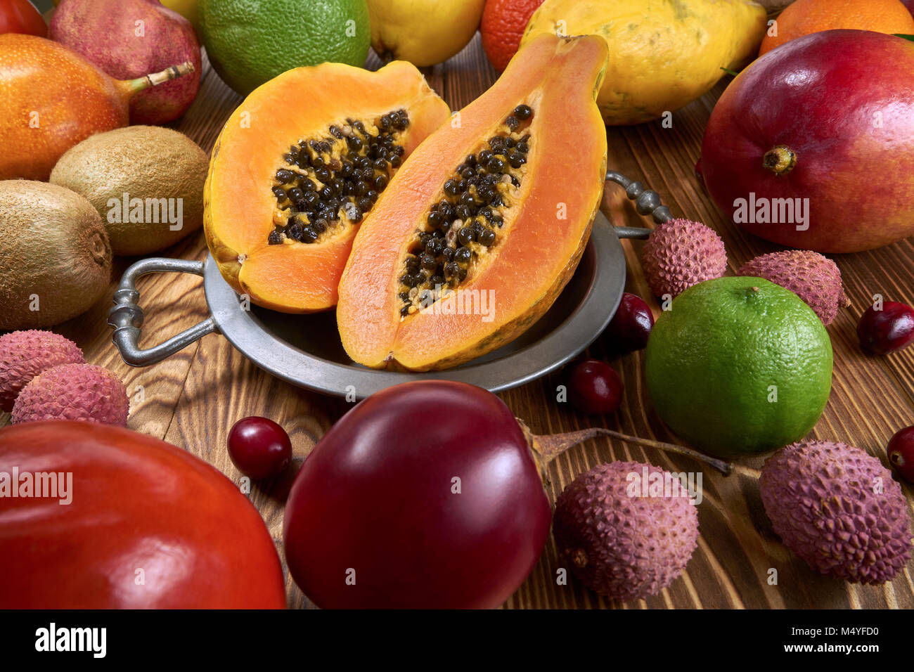 Papaya fruit on a tin bowl, around a lot of fruits of a different species - Stock Image