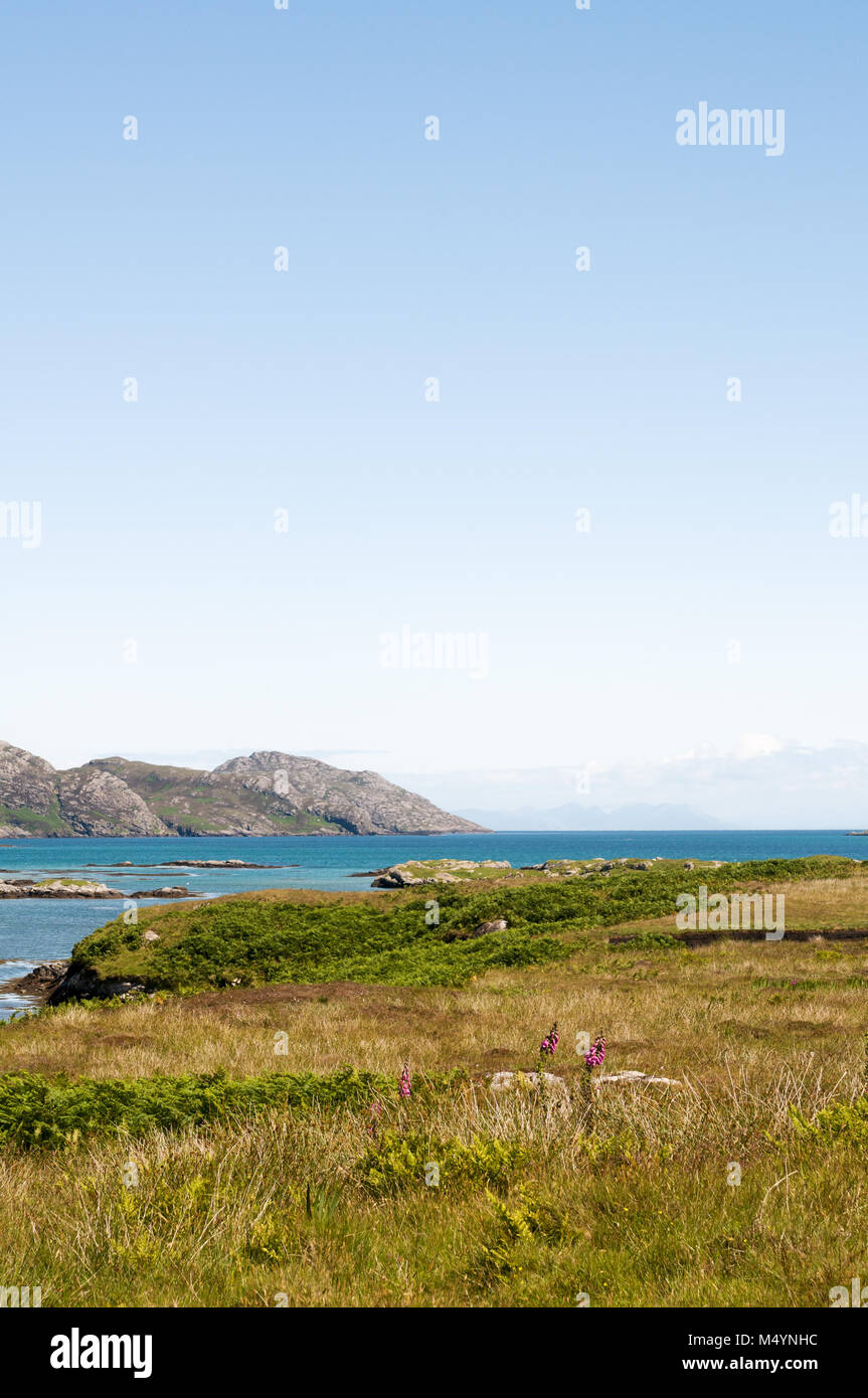 View over the grasslands to the hills of South Glendale on the Isle of South Uist, Outer Hebrides with the Minch - Stock Image