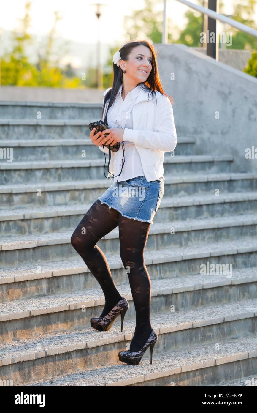 Young woman legs spike spiked heels denim short mini skirt Stock Photo