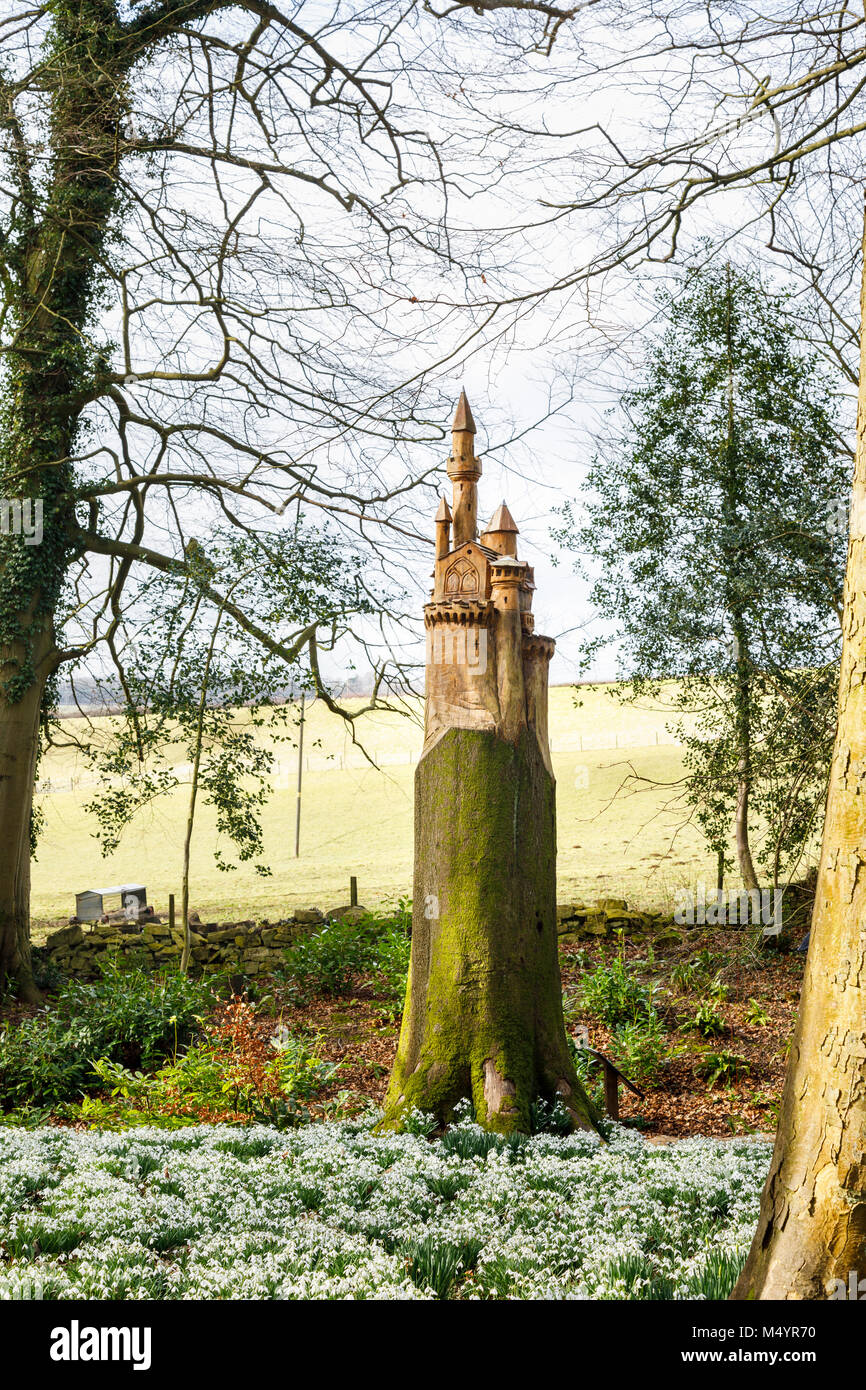 Carpet of snowdrops and nesting box carving of a castle on the stump of a dead tree trunk in woodland, Painswick - Stock Image