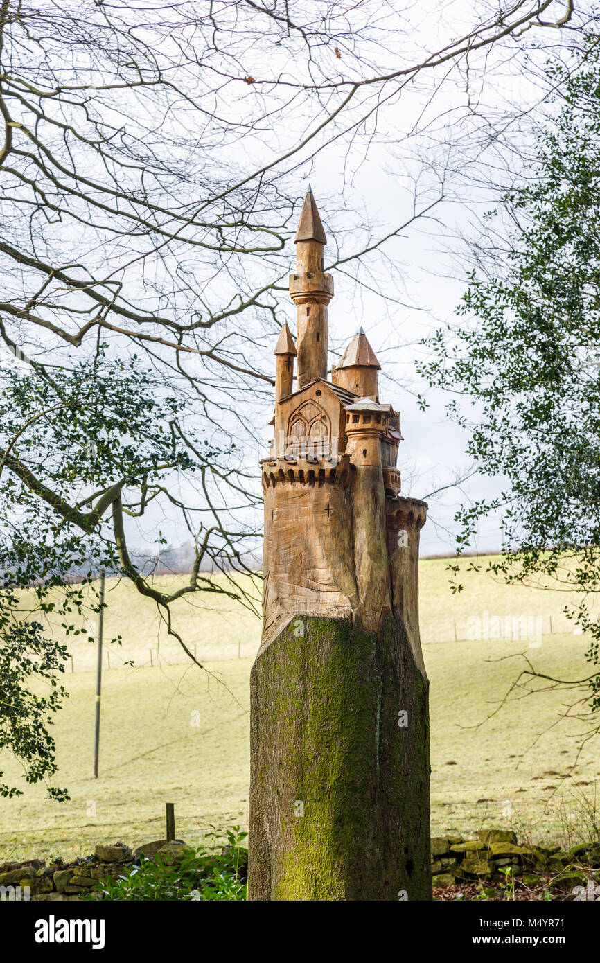 Carving of a castle made into a bird box on the stump of a dead tree trunk in woodland, Painswick Rococo Garden, - Stock Image
