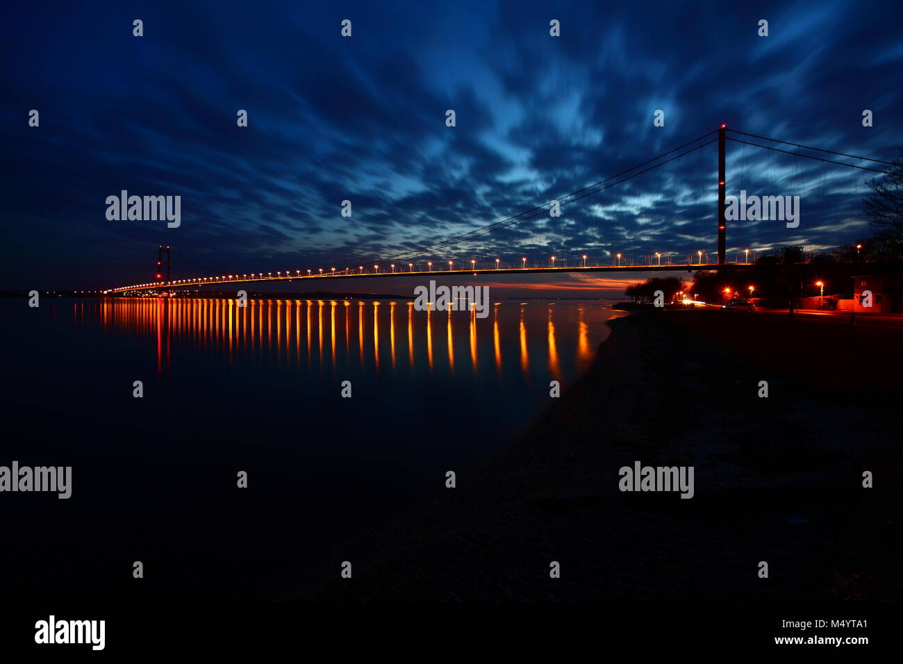 The Humber Bridge reflecting in the River Humber at night Stock Photo