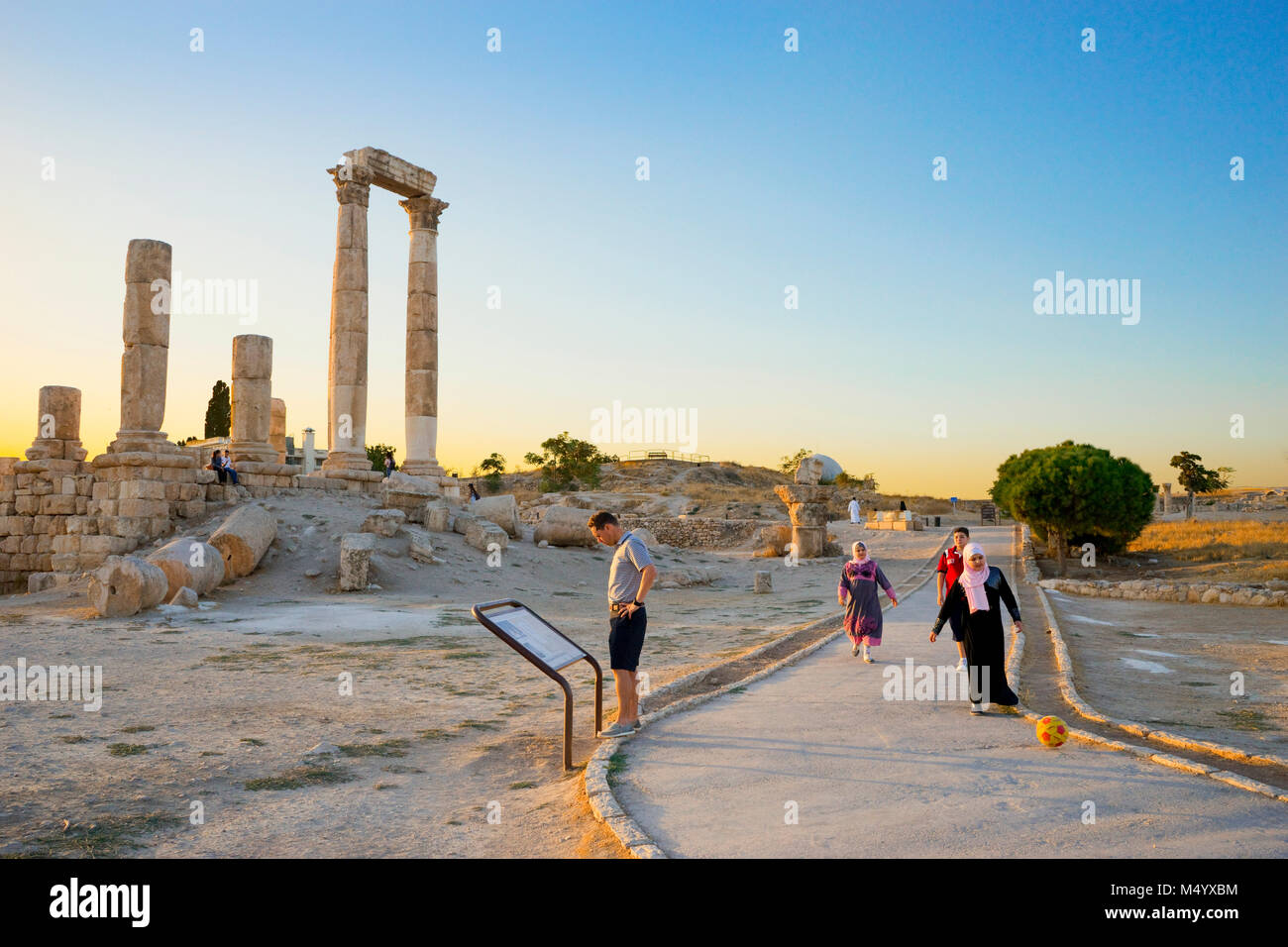 Man reading information sign and kids playing with soccer ball at Temple of Hercules in Amman Citadel, Amman, Jordan - Stock Image