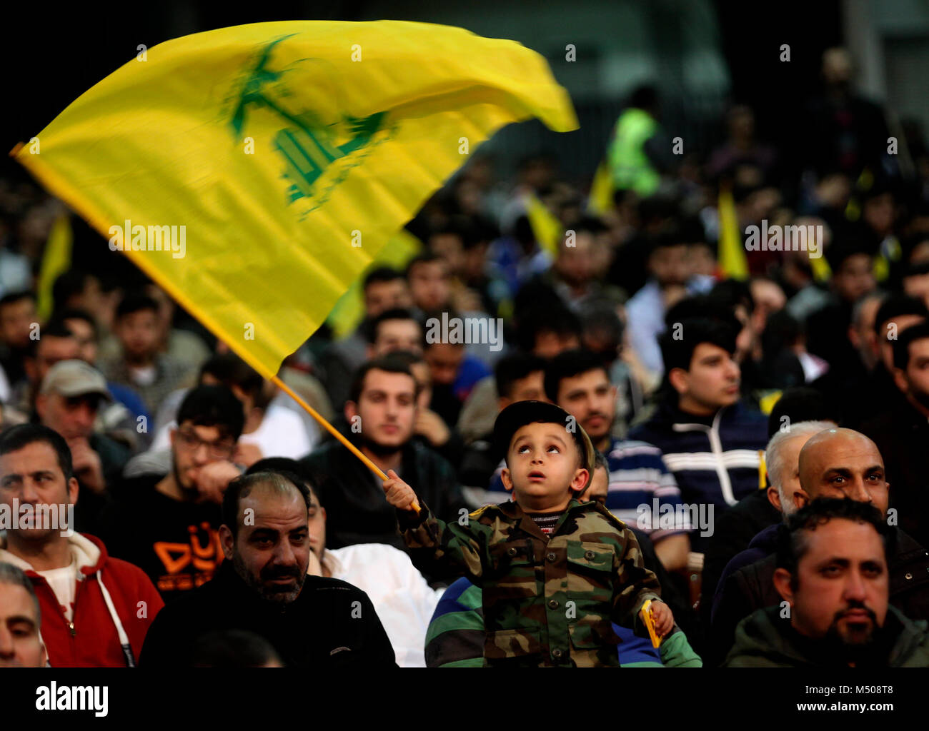 16 Febuary 2018, Lebanon, Beirut: A child sways a Hezbollah flag during a memorial service in the honour of three - Stock Image