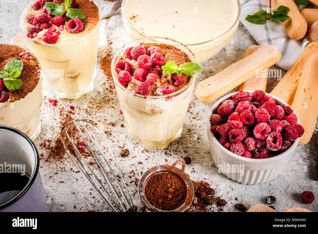 Cooking Italian food dessert Tiramisu, with all the necessary ingredients cocoa, coffee, mascarpone cheese, mint - Stock Image
