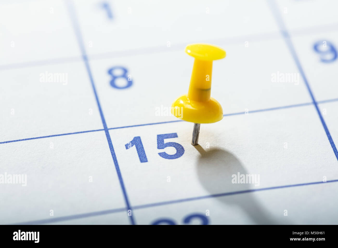Close-up Of Yellow Thumbtack Stuck On Date 15th In Calendar - Stock Image