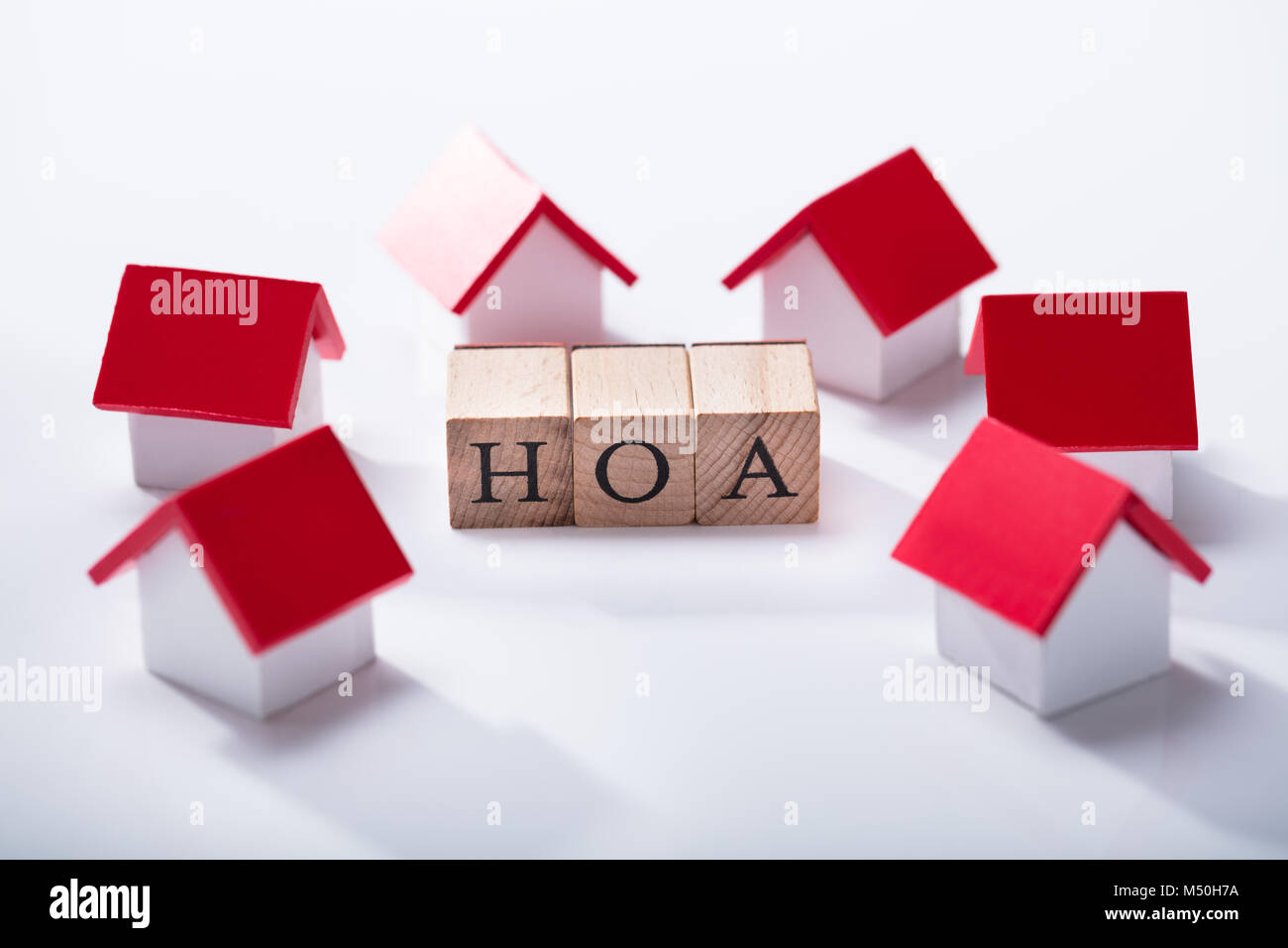 Homeowner Association Wooden Blocks Surrounded With Miniature House Models Over The White Background - Stock Image