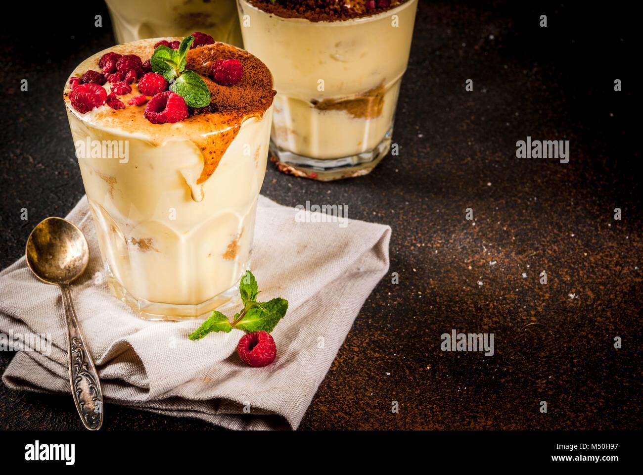 Three portioned glass with Italian dessert Tiramisu, with mint and raspberries, on dark rusty background.  Copy - Stock Image