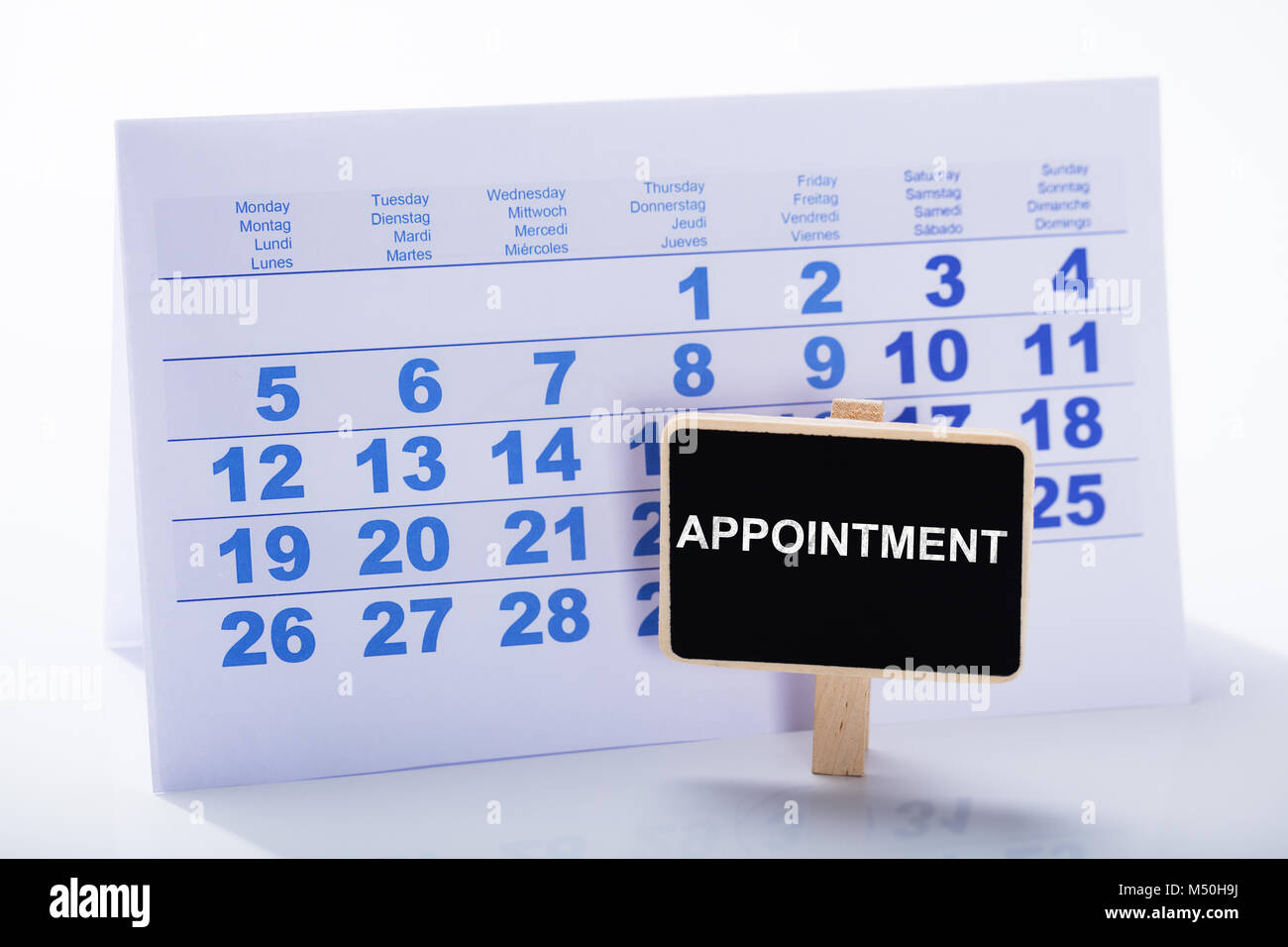 Miniature Appointment Placard In Front Of Calendar Against White Background - Stock Image