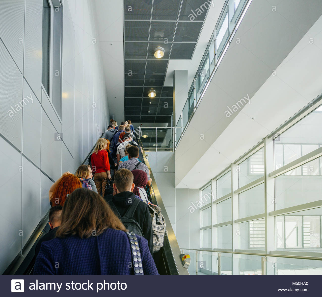 Passengers commuting on the escalator in modern airport terminal - Stock Image