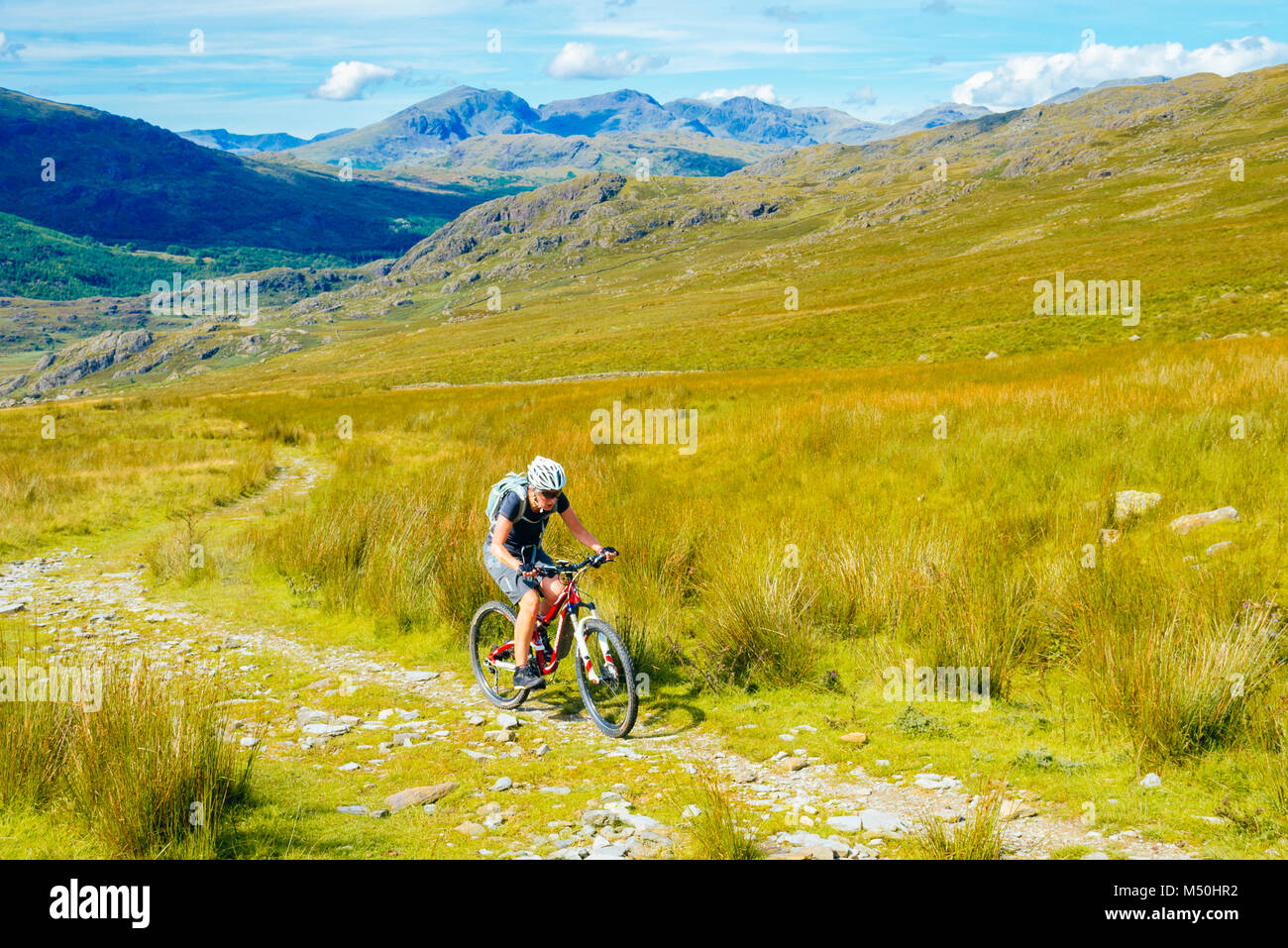 Female mountain biker climbing the Walna Scar Road above the Duddon Valley in the English Lake District - Stock Image