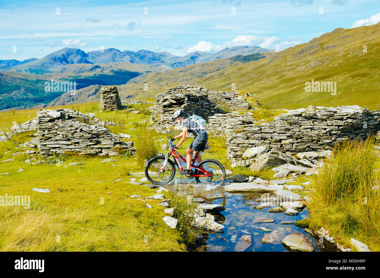 Female mountain biker passing quarry ruins at Walna Scar Quarries in the English Lake District with Scafell and - Stock Image