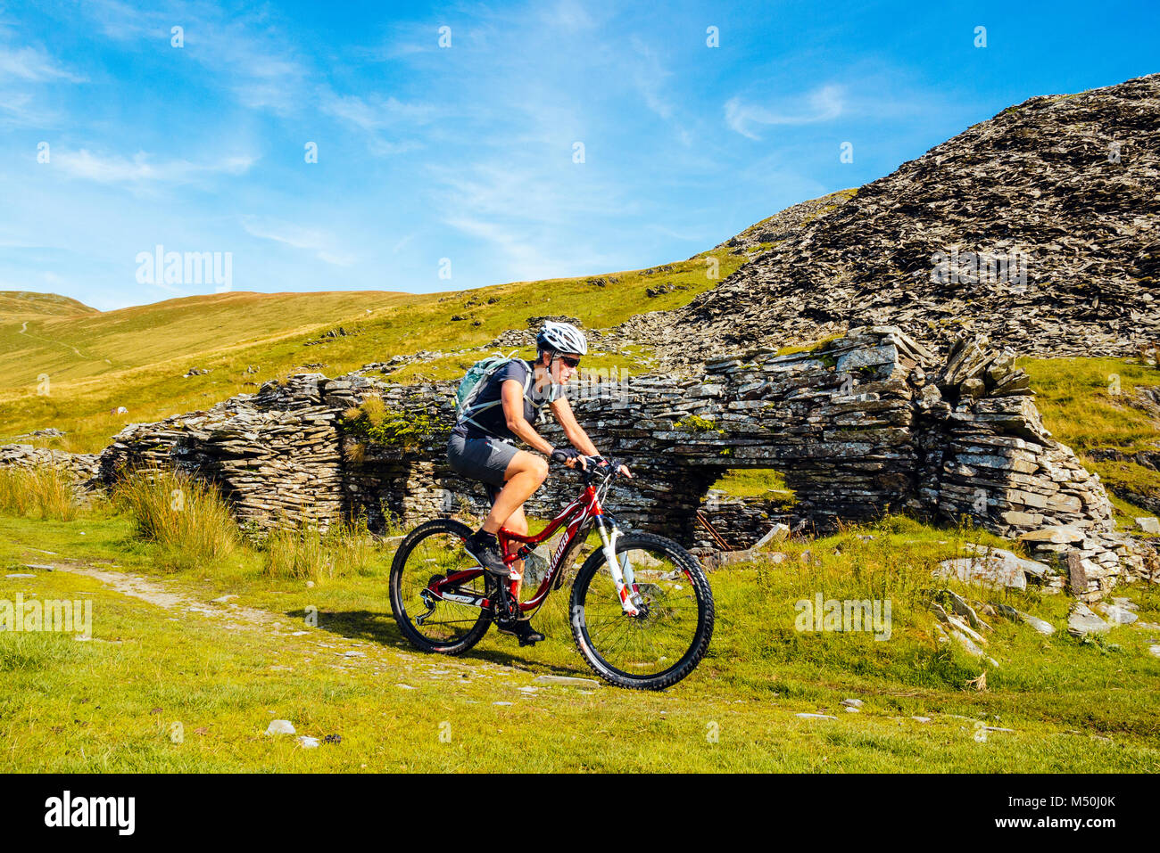 Female mountain biker passing quarry ruins at Walna Scar Quarries in the English Lake District - Stock Image