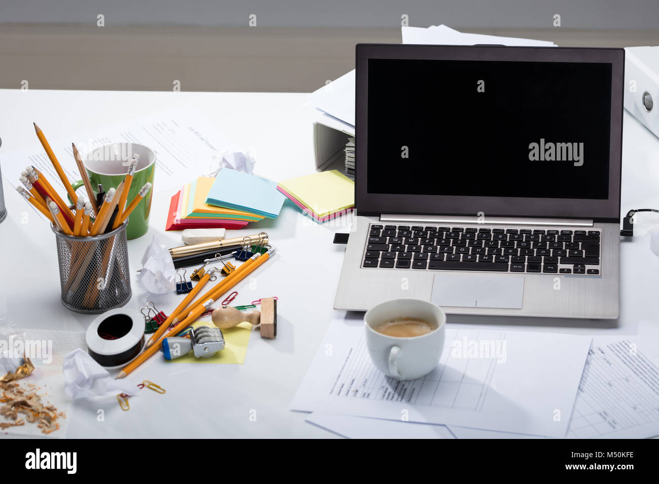 Laptop And Coffee Cup On The Document Paper Over The Messy Desk In The Office - Stock Image