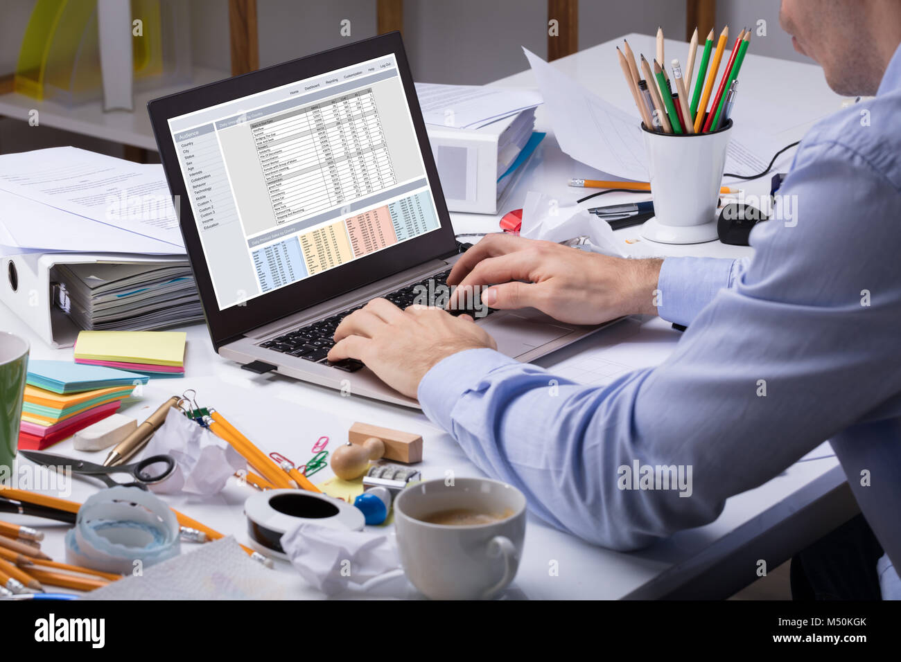 Close-up Of Businessman Using Laptop Over The Messy Desk At Workplace In The Office - Stock Image