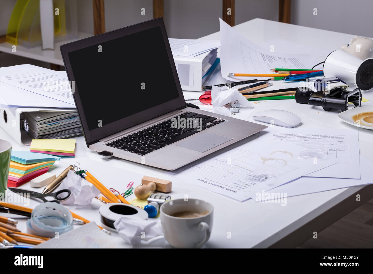 An Open Laptop On The Messy Desk With Coffee Cup And Documents At Workplace - Stock Image