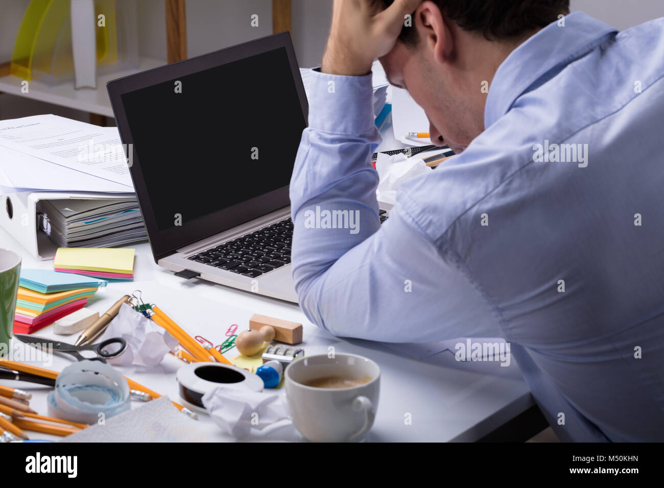 Close-up Of Stressful Businessman With Laptop On Messy Desk At Workplace - Stock Image