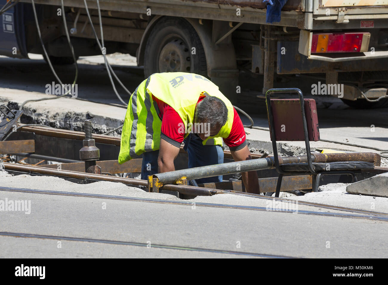 Worker construct asphalt road and railroad lines - Stock Image